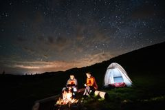 Tourists near campfire and tent under night starry sky Stock Photos