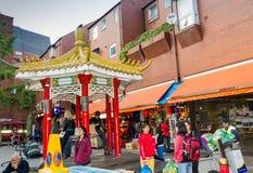 Tourists near Chinese souvenirs shop at China town in Soho, London, UK. LONDON, UK - JUNE 7, 2015: Tourists near Chinese souvenirs shop at China town in Soho Royalty Free Stock Photo