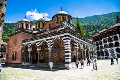 Tourists near the church in famous Rila Monastery, Bulgaria Stock Photos