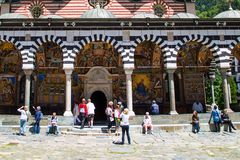 Tourists near the church in famous Rila Monastery, Bulgaria Stock Photography