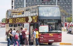 Tourists near the double-decker tour bus stock image
