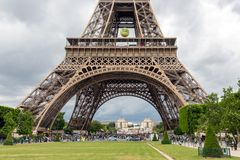 Tourists near Eiffel Tower with big tennis ball of Roland Garros in Paris, France Royalty Free Stock Photo