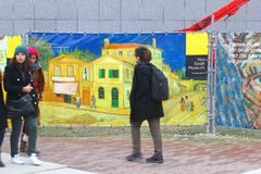 People walk along a sign to the Vincent van Gogh Museum, Amsterdam Royalty Free Stock Photography
