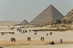 Tourists near famous Egyptian pyramids Royalty Free Stock Photos