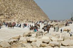 Tourists near famous Egyptian pyramids Stock Photography