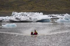Tourists near Frozen Ice from Glacier in Iceland stock photo