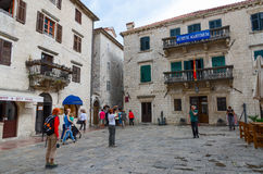 Tourists are near Maritime Museum on Square of Old Town, Kotor, Royalty Free Stock Images