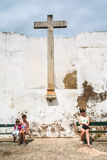 Tourists near old medieval cross in white wall royalty free stock images