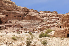 Tourists near the roman-era amphitheater carved into the pink sandstone at Petra Stock Image