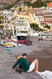 Tourists near the small harbor of Positano. Positano, Italy - May 24, 2016: Tourists near the small harbor with the Cathedral in the background. Millions of Royalty Free Stock Photo