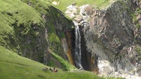 Tourists near a waterfall stock video