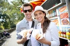 Tourists in new york eating fast food in the street. Tourists in New York city eating hot dogs stock image