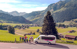 Tourists next to a bus. In Switzerland. Alpine mountains in the background are on a cloudy day. It´s a editorial  picture Royalty Free Stock Photography