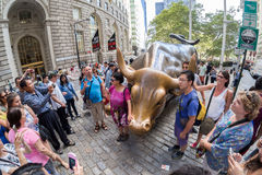 Tourists next to the Wall Street Bull sculpture in New York City Stock Images