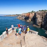 Tourists observe Boca do Inferno of Cascais. Cascais, Portugal - August 14, 2017: Tourists observe Boca do Inferno from coastal viewpoint. Seaside cliffs with Stock Photography