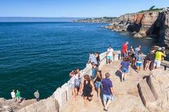 Tourists observe Boca do Inferno. Seaside cliffs. Cascais, Portugal - August 14, 2017: Tourists observe Boca do Inferno. Seaside cliffs with the Hell`s Mouth Royalty Free Stock Photo