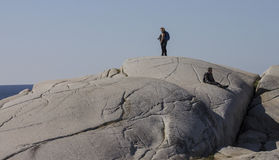Tourists observe the rocky coast of Peggy's Cove Nova Scotia September 2014. Stock Photography