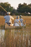 Tourists in the Okavango Delta - Botswana. Tourists in a makoro in the reeds of the Okavango Delta in Botswana Stock Photography