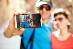 Tourists in the old town. Couple tourists  walking in the old town and take selfie, focus on the phone Royalty Free Stock Images