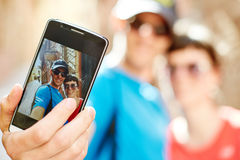 Tourists in the old town. Couple tourists  walking in the old town taking selfie. Focus on the phone Royalty Free Stock Photography