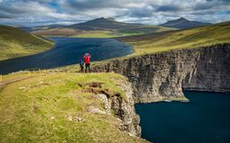 Tourists over Sorvagsvatn lake cliffs over the ocean under the clouds, Faroe Islands