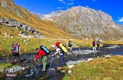 Hiking tourists overcome a mountain river Stock Photography