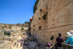 Tourists overlook a Herodian street below Robinson`s Arch, an unusually wide stone arch, which once stood at the southwestern. Corner of the remains of the royalty free stock images