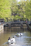 Tourists paddle in water bikes in Amsterdam canal in spring Stock Images