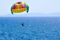 Tourists parasailing on aegean sea in Kusadasi, Turkey. Two tourists parasailing on aegean sea in Kusadasi, Turkey with mountains in distance Royalty Free Stock Photo