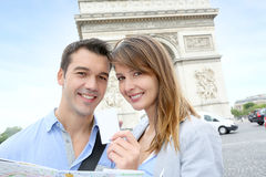 Tourists in Paris. Cheerful couple holding tourist ticket by the Arch of Triumph Stock Photo