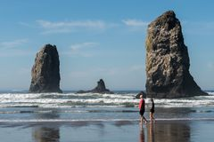 Tourists pass by the unique rocks in the water of the Pacific Ocean in Cannon Beach, Oregon, USA. stock photo