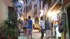 Tourists passing by souvenir shops in Rovinj stock video