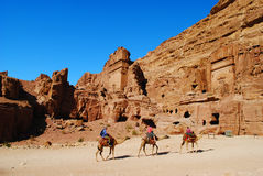 Tourists passing the Uneishu Tomb on the Street of Facades in Petra, Jordan Royalty Free Stock Photography