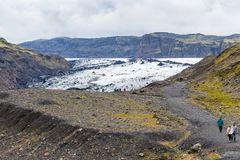 Tourists on path to Solheimajokull glacier. KALTA GEOPARK, ICELAND - SEPTEMBER 9, 2017: tourists on path to Solheimajokull glacier South glacial tongue of Stock Photography