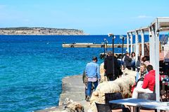 Tourists at a pavement cafe, Mellieha. Tourists relaxing at a pavement cafe with views across the bay, Mellieha, Malta, Europe Stock Photography
