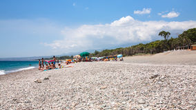 Tourists on pebble beach San Marco on Ionian Sea. CALATABIANO, ITALY - JULY 6, 2011: tourists on pebble beach San Marco on Ionian Sea coast in Sicily. This is Stock Photos