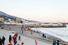 Tourists on pebble beach of Yalta city in evening Stock Images