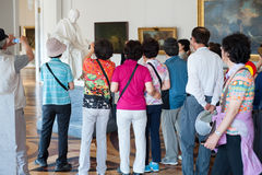 Tourists photograph statue of Voltaire in Hermitage Royalty Free Stock Photography