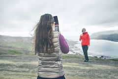 Tourists photographing each other against the background of a beautiful landscape in Iceland. Field with blooming lupines, mountains and fjords on the Royalty Free Stock Images