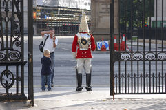 Tourists photographing a royal guard Stock Photography