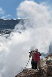 Tourists photographing smoking fumarole on crater active volcano Royalty Free Stock Images