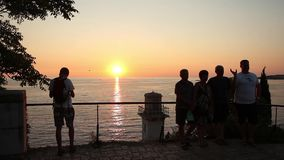 Tourists photographing sunset stock footage