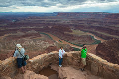 Tourists and Photography Desert Canyon Landscape. DEAD HORSE POINT STATE PARK, UTAH - SEPT 28, 2014: Three tourists on Dead horse point outlook, one photographer stock image
