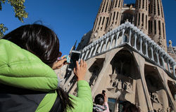 Tourists picturing sagrada familia cathedral. Two girls use their smartphones to take photographs of the Sagrada Familia cathedral designed by architect Antonio Royalty Free Stock Photos