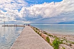 Tourists on pier with cloudy sky in eastern shore of Lake Garda Royalty Free Stock Images