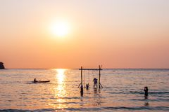 Tourists play in the water sea during the sunset at area ao bang bao Koh kood island Trat, Thailand.  royalty free stock photos