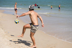 Tourists playing with ball on the beach Stock Image