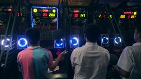 Tourists Playing Basketball and Throwing Ball at Arcade Machine in Game Zone MBK Shopping Center. 4K. Bangkok, Thailand. 15 NOV 2017 stock footage