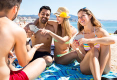 Tourists playing cards on beach. Two couples of tourists on vacation sitting on a beach towel on sand near sea and playing card games stock photography