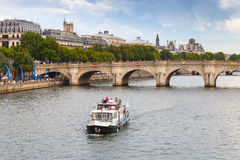 Tourists on the pleasure boat goes near Pont Neuf in Paris Royalty Free Stock Photo